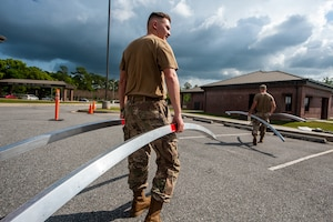 A photo of an Airman walking while holding tent bars.