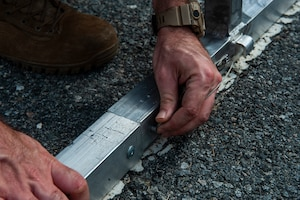 A photo of an Airman connecting tent support rods