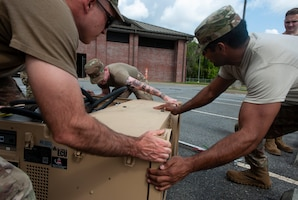 A photo of Airmen moving an air conditioning unit.