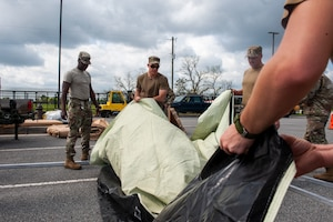 A photo of Airmen unfolding a tent floor mat.