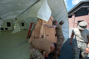 A photo of Airmen setting up a tent