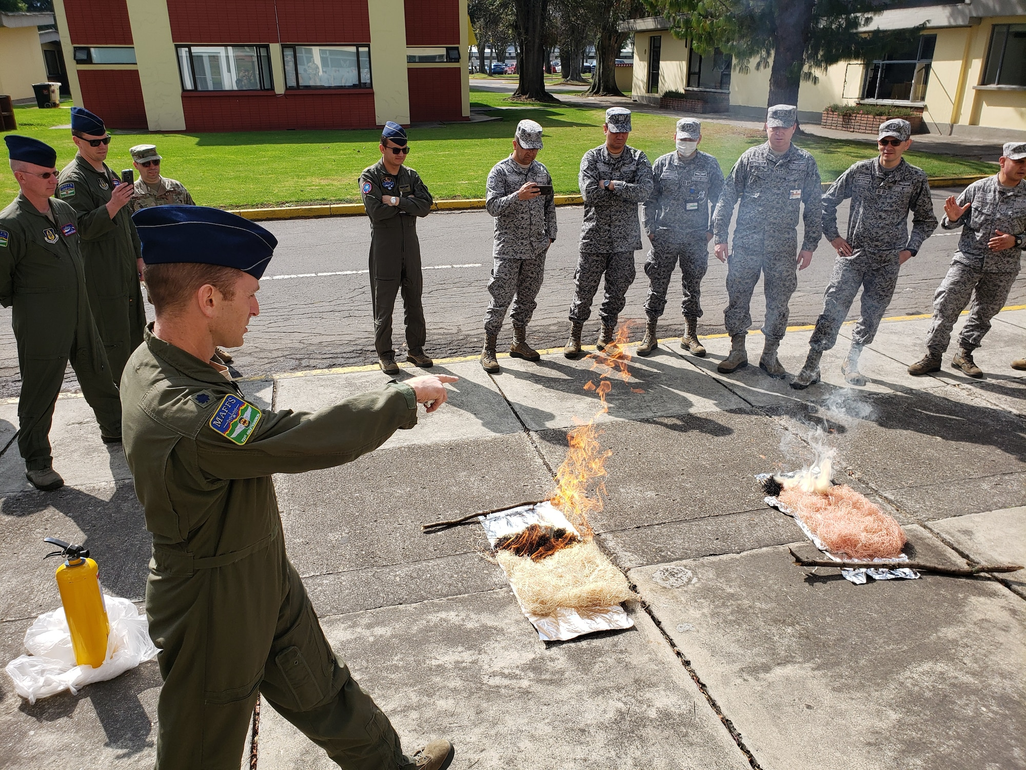 U.S. Air Force Lt. Col. Richard Pantusa, 731st Airlift Squadron Modular Airborne Fire Fighting Systems instructor pilot from Peterson Air Force Base, Colorado, demonstrates the effectiveness of fire retardant in combating forest fires to members from the Fuerza Aerea Colombiana. Employing an aerial firefighting capability will help the FAC in combatting wild fires, both internally and internationally. The specialized training, provided by the U.S. Air Force Reserve Command personnel, was a stepping stone to future work with the FAC on further enhancing this capability. (Courtesy Photo)
