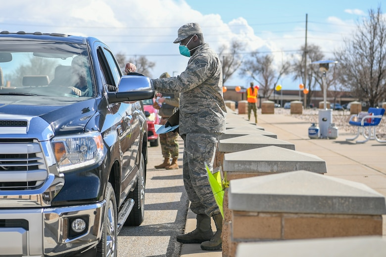 Senior Airman Elijah Thompkins, 75th Medical Group, hands a prescription over to a beneficiary March 23, 2020, at Hill Air Force Base, Utah. The 75th Medical Group Satellite Pharmacy is providing curbside service until further notice in front of the Base Exchange shopping center in support of social distancing recommendations and to increase efforts to mitigate further spread of the novel coronavirus.(U.S. Air Force photo by Cynthia Griggs)