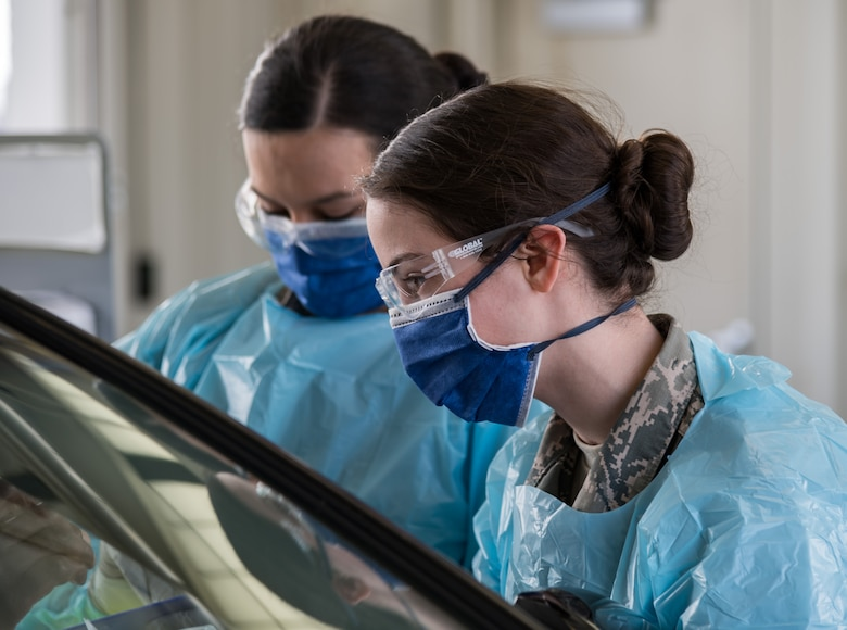 U.S. Air Force Airman 1st Class Christina Noel, right, and Hope Vusich, left, both assigned to the 436th Operational Medical Readiness Squadron ask a base clinic patron three questions as part of the screening process at the main gate on Dover Air Force Base, Delaware, March 18, 2020. Team Dover medical personnel initiated preventative measures against the spread of COVID-19. (U.S. Air Force photo by Roland Balik)