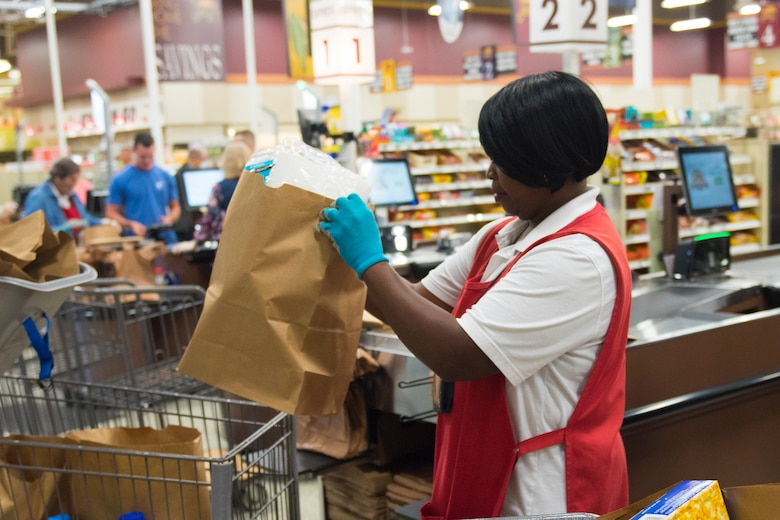 Shirley Burgohy, a head bagger at the Air Base Commissary, assists customers checking out at Joint Base Charleston S.C., March 24, 2020.