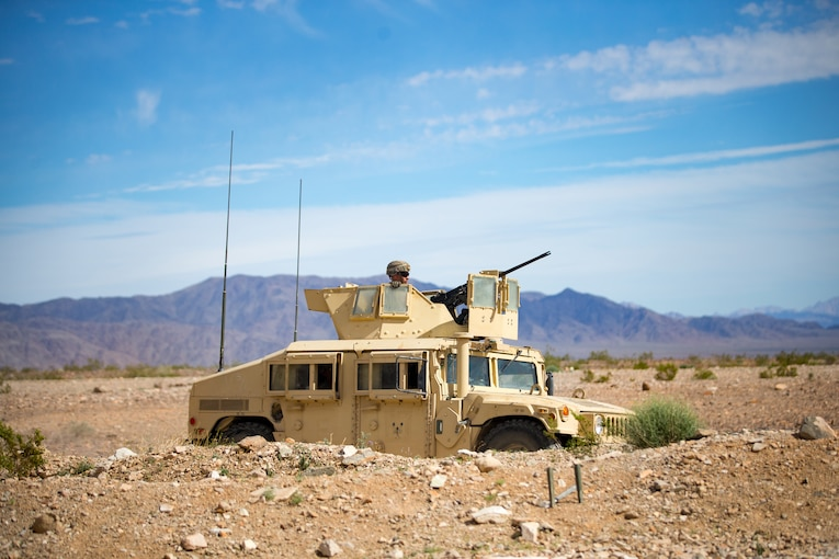 A Marine sits in a military vehicle in the desert.