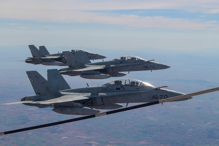 Spanish Air Force F18 Hornets with the 11th Wing fly in formation next to a U.S. Marine Corps KC-130J