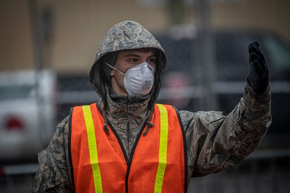 A New Jersey Air Guard Airman from the 108th Wing provides traffic control at a COVID-19 Community-Based Testing Site at the PNC Bank Arts Center in Holmdel, N.J., March 23, 2020.  The testing site, established in partnership with the Federal Emergency Management Agency, is staffed by the New Jersey Department of Health, the New Jersey State Police, and the New Jersey National Guard. (U.S. Air National Guard photo by Master Sgt. Matt Hecht)