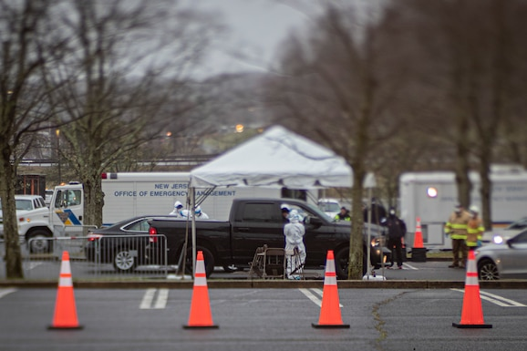 Medical technicians process patients at a COVID-19 Community-Based Testing Site at the PNC Bank Arts Center in Holmdel, N.J., March 23, 2020.  The testing site, established in partnership with the Federal Emergency Management Agency, is staffed by the New Jersey Department of Health, the New Jersey State Police, and the New Jersey National Guard. (U.S. Air National Guard photo by Master Sgt. Matt Hecht)