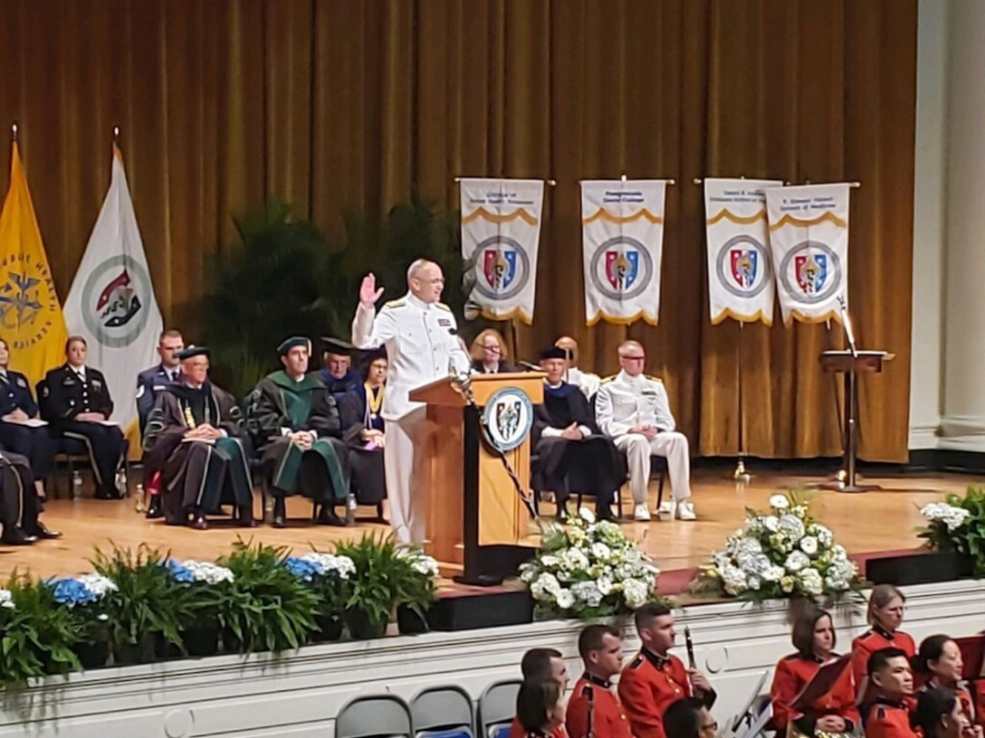 Navy admiral holds up his right hand to administer an oath while standing behind a lectern on an auditorium stage.