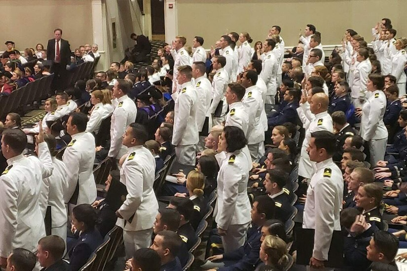 Service members stand at their seats in an auditorium and raise their right hands.