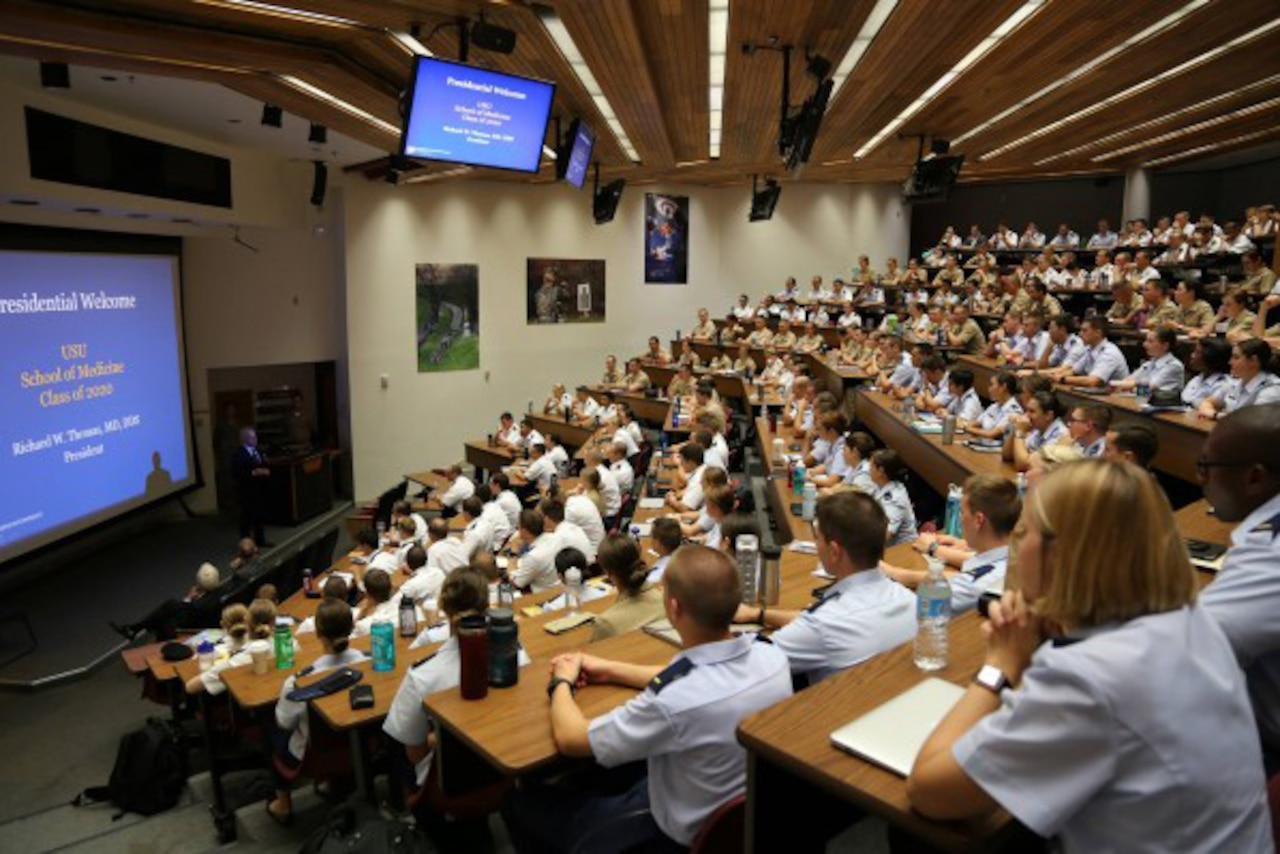 Medical students fill an auditorium lined with wall-mounted screens.