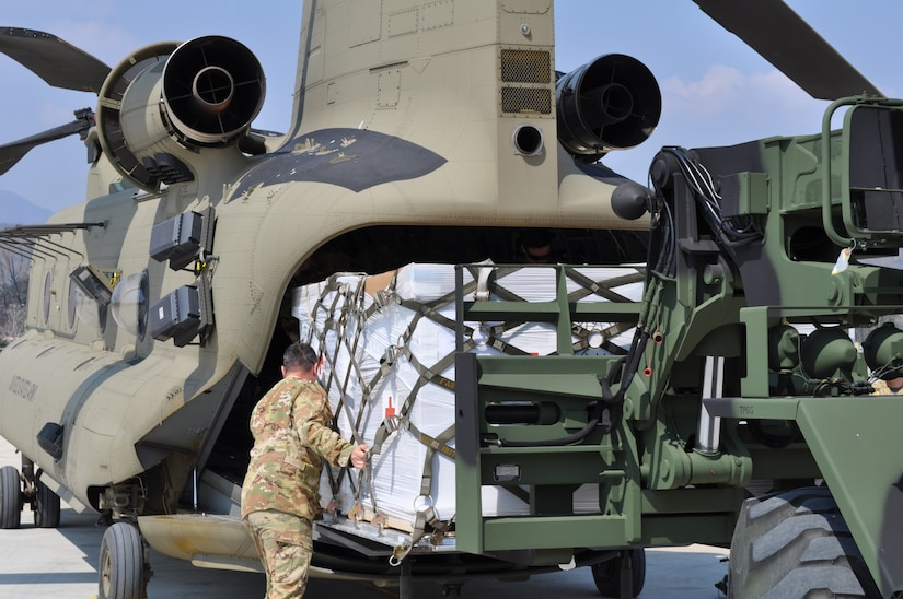 Soldiers from the U.S. Army Medical Materiel Center-Korea's 563rd Medical Logistics Company loads Class VIII medical supplies onto a CH-47 helicopter with guidance from the 2ID/2CAB crew chief on March 24, 2020.
