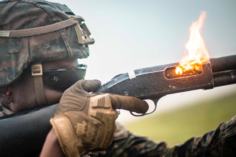 A Marine fires a shotgun with flames coming from the chamber.