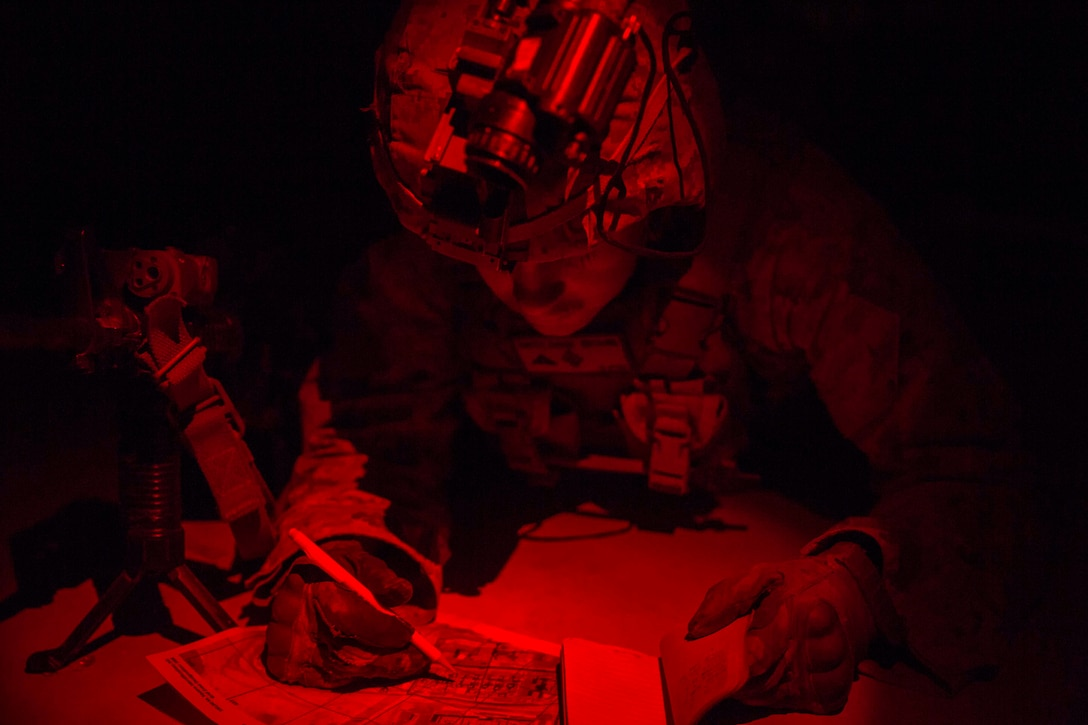 A Marine illuminated by red light plots points on a map.