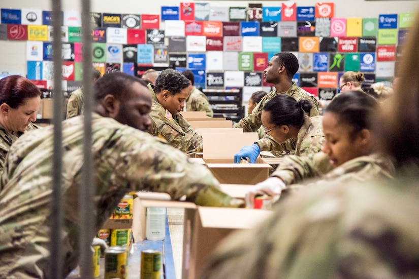 Service members wearing gloves put food into boxes.