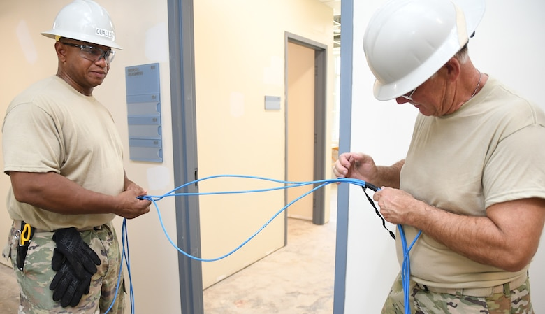U.S. Air Force Tech. Sgt. Antonio Qualls and Master Sgt. George Harvey, cable installers with the 202d Engineering Installation Squadron (202d EIS), Georgia Air National Guard, run cable at Muñiz Air National Guard Base, Carolina, Puerto Rico, to assist the Puerto Rican Air National Guard with the installation of the network infrastructure for a new, multi-use building, Aug. 14, 2019. The role of the 202d EIS is to install, repair and service the sophisticated command, control, communications, intelligence, intelligence, surveillance, and air reconnaissance at Air Force installations worldwide. U.S. Air National Guard photo by Barry Bena.