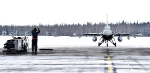A crew chief from the 354th Aircraft Maintenance Squadron marshals in an F-16 Fighting Falcon from the 18th Aggressor Squadron on Eielson Air Force Base, Alaska, March 24, 2020. Airmen from the 354th AMXS are continuing to maintain aircraft during the COVID-19 global pandemic while implementing the necessary health precautions to help minimize the spread of the virus.(U.S. Air Force photo by Senior Airman Beaux Hebert)