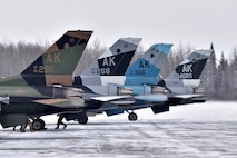 Four F-16 Fighting Falcons from the 18th Aggressor Squadron sit on the runway for final maintenance checks prior to taking off from Eielson Air Force Base, Alaska, March 24, 2020. Maintainers work around the clock to ensure the 354th Fighter Wing's jets are always ready to execute the mission. (U.S. Air Force photo by Senior Airman Beaux Hebert)