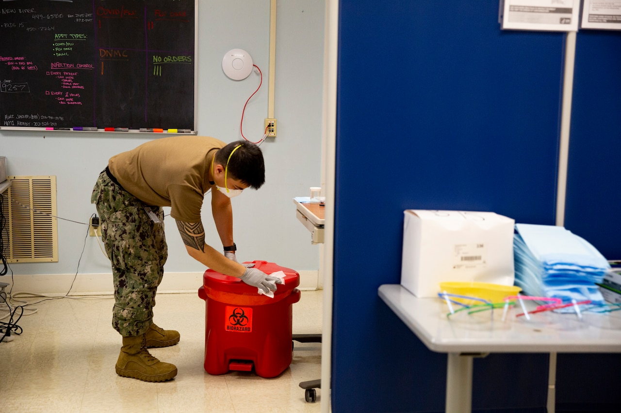 A person scrubs to disinfect equipment.