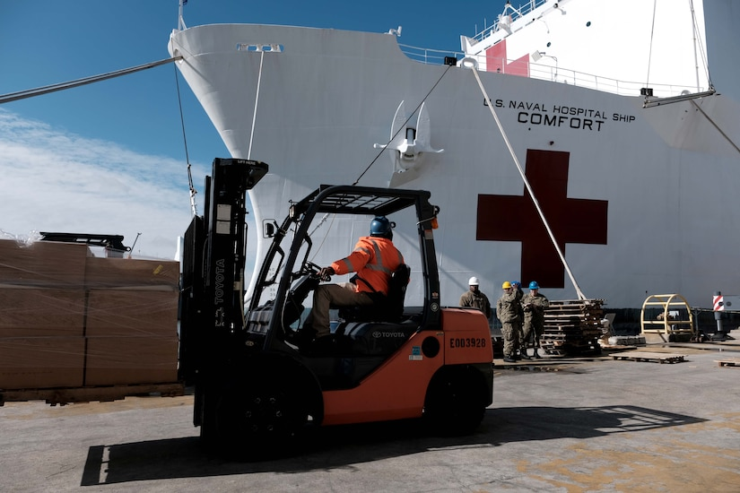 A forklift operator positions his load on dock in front of a ship.