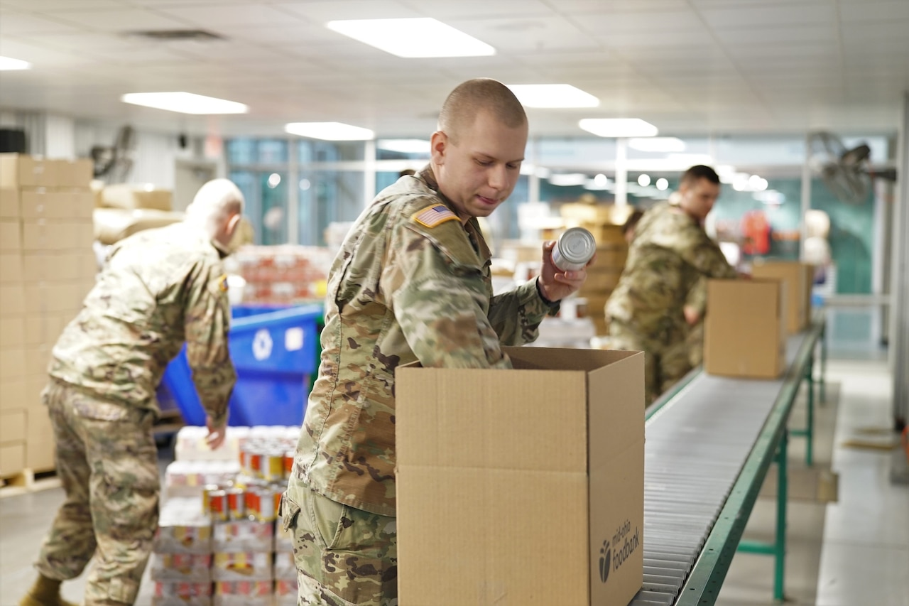 Soldier places cans of food into a box.