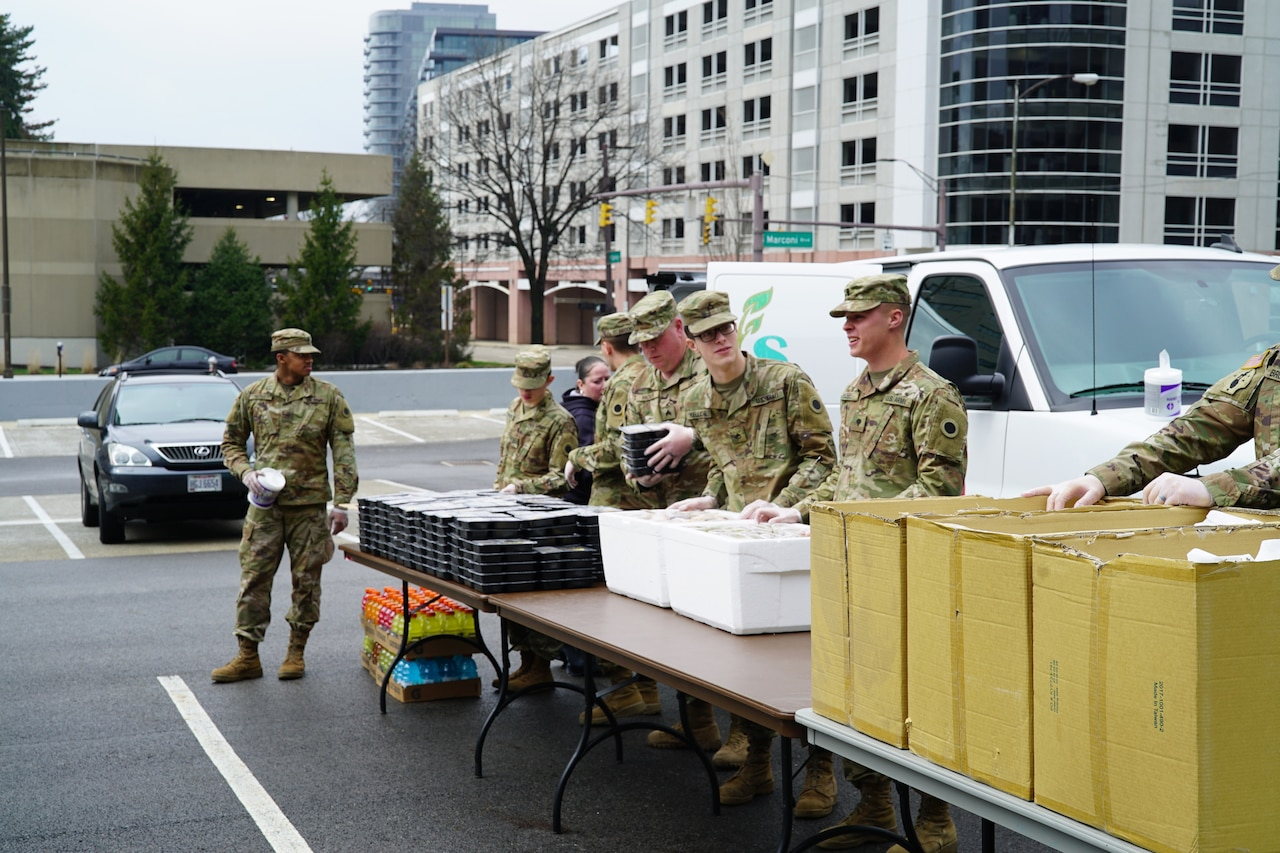 Soldiers move packaged hot meals to a long table.