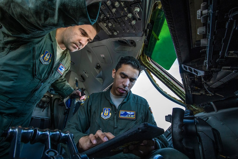 Maj. Daniel M. Brillman, left, looks on as 2nd Lt. Peter A. Ruiz, both KC-10 Extender pilots with the 76th Air Refueling Squadron, 514th Air Mobility Wing at the time, inputs data prior to a refueling mission at Joint Base McGuire-Dix-Lakehurst, New Jersey, in 2018. (Master Sgt. Mark C. Olsen)