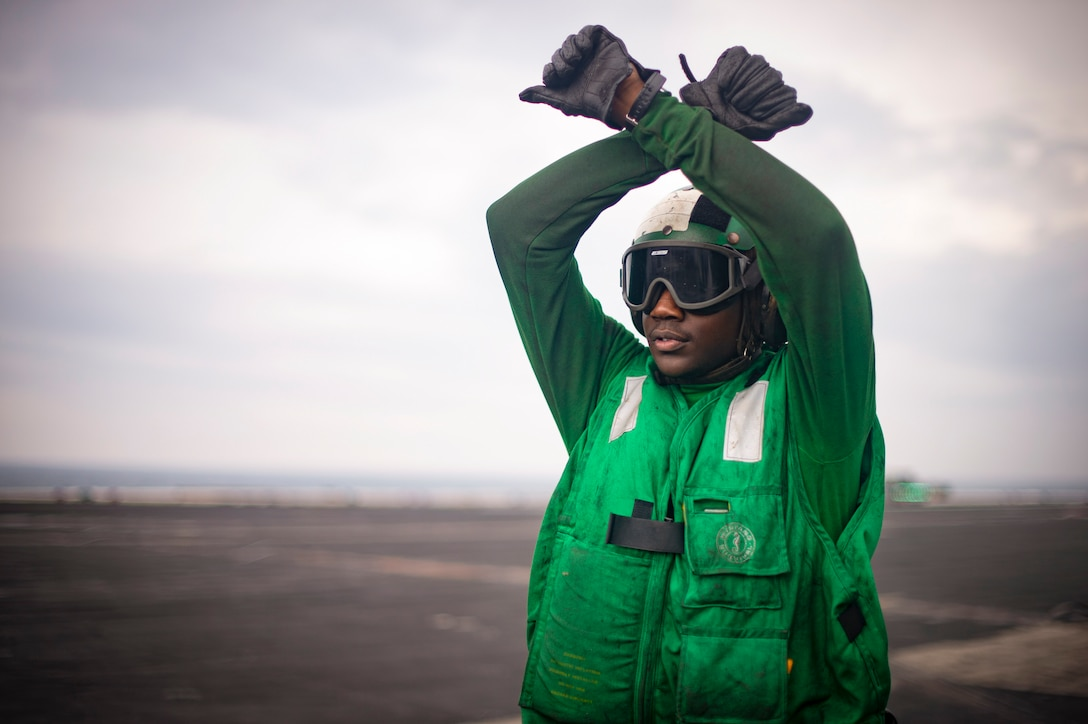 A sailor wearing a green vest and helmet signals to an aircraft.
