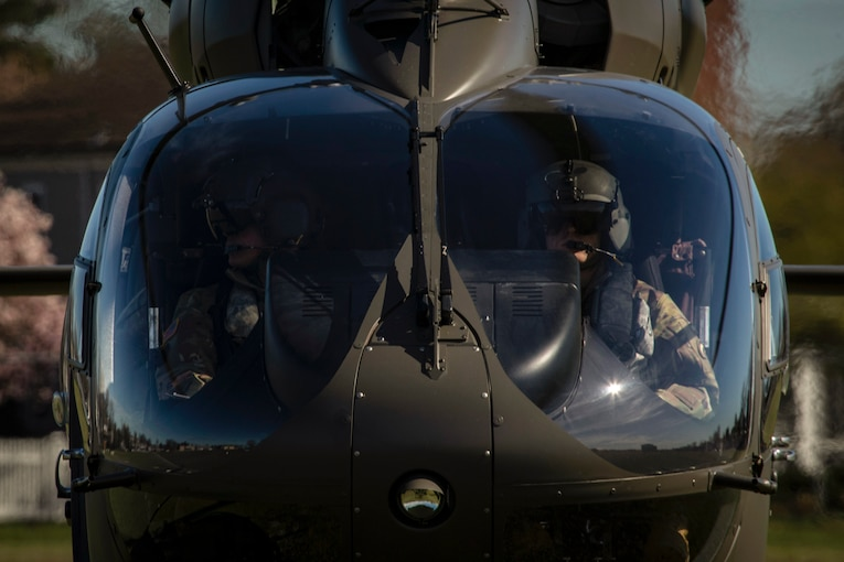 Two soldiers look out from the cockpit of a Lakota helicopter.