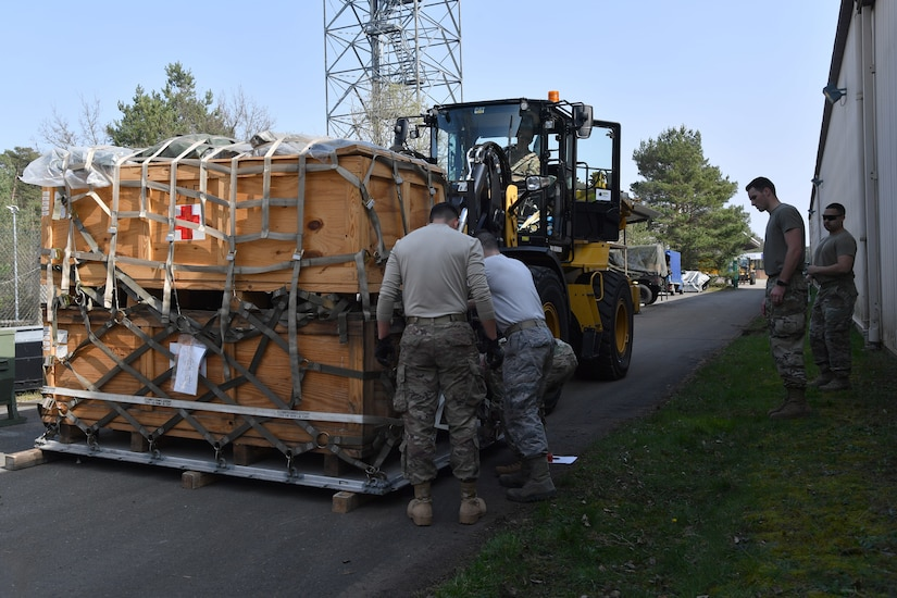 Airmen secure a pallet of supplies to a forklift.