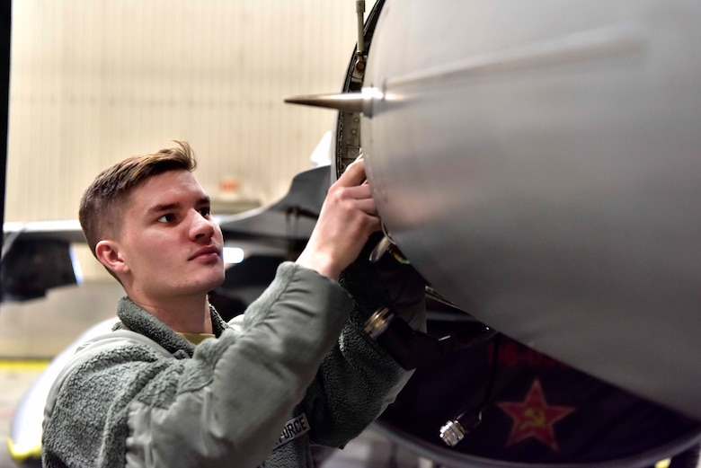 Airman 1st Class Cody Cornett, a 354th Aircraft Maintenance Squadron avionics specialist, works on an F-16 Fighting Falcon on Eielson Air Force Base, Alaska, March 24, 2020. In accordance with Center for Disease Control recommendations, Eielson Airmen are mandated to practice health safety measures including social distancing, consistent hand washing and sanitizing work areas at the start and end of their shift. (U.S. Air Force photo by Senior Airman Beaux Hebert)