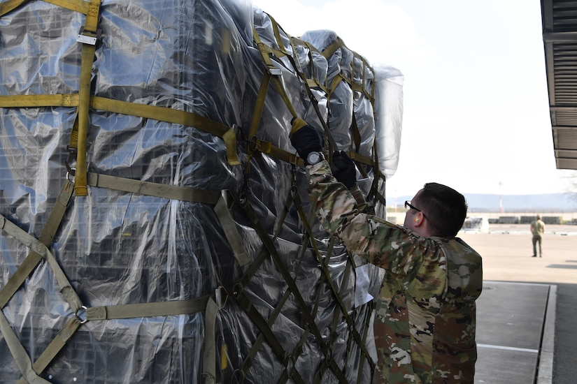 An Airman inspects the straps securing medical supplies to a pallet.