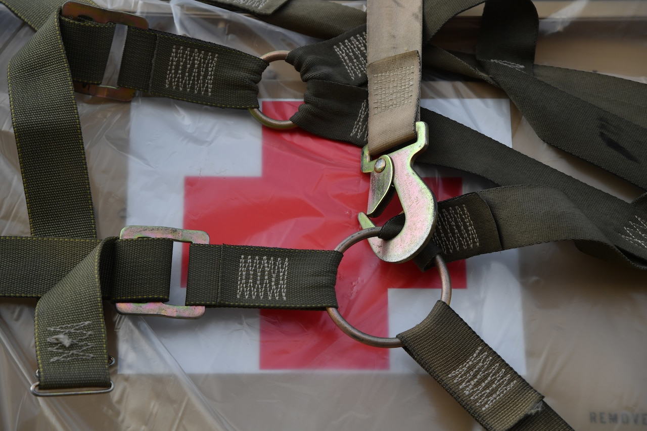 Straps secure a box of supplies labeled with a red cross on a pallet.