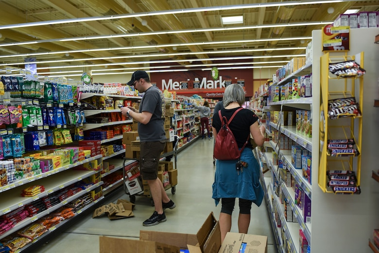 Airmen and families volunteer in the Commissary at Spangdahlem Air Base, Germany, March 23, 2020. Volunteers throughout the base community offered to box and stock shelves because of the current high demand of products. (U.S. Air Force photo by Senior Airman Melody W. Howley)