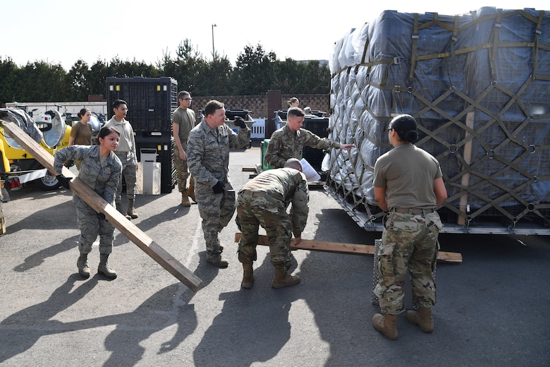 Airmen work around a pallet of medical supplies.