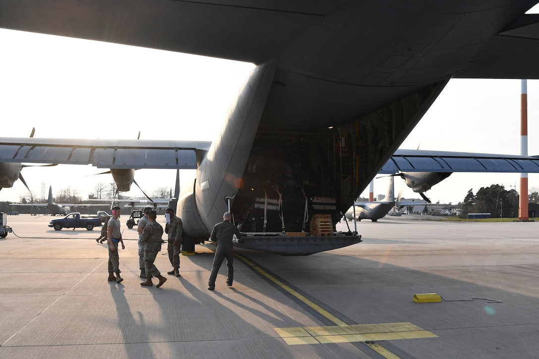 Airmen stand next to a cargo plane loaded with medical supplies.