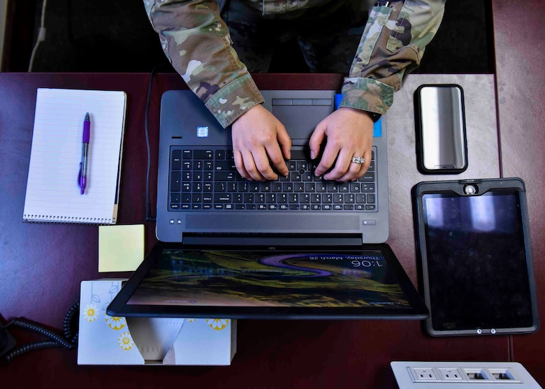 A U.S. Air Force member teleworks from home to practice social distancing. Staying home if sick, and self-quarantining if exposed to those with COVID-19 symptoms (coughing, fever, shortness of breath), and teleworking when possible has been highly encouraged in both the civilian and military sectors. (U.S. Air Force photo by Airman 1st Class Kiaundra Miller)