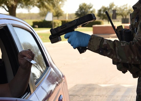 U.S. Air Force Airman 1st Class Sandy Amezquita, 17 Security Forces Squadron installation entry controller, scans a common access card at the Jacobson Gate on Goodfellow Air Force Base, Texas, March 25, 2020.  Goodfellow's base commander declared a Public Health Emergency and limited movement for military personnel in accordance to Tier 1's policies and procedures. Goodfellow was in Health Protection Condition BRAVO with no confirmed COVID-19 cases. (U.S. Air Force Photo by Airman 1st Class Abbey Rieves)