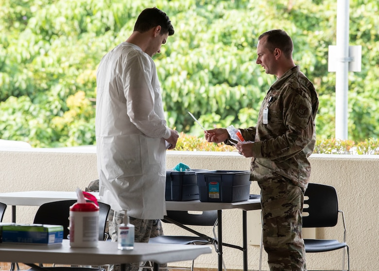 嘉手納基地第18医療群所属の空軍兵士が新型コロナウイルスの検査を実施している様子(2020年3月20日撮影)。米疾病対策センターが公表した最新の指針を基に、第18医療群は検査件数を増やした。検査を受けた者(PUI)は、衛生担当官の指示を受けて自宅待機し、家族へ感染しないための助言を受ける。担当官は検査対象者に聞き取りを行い、濃厚接触者リストを作成する。担当官は、濃厚接触者と疑われる者に連絡し、14日間の移動制限を指示する。濃厚接触者とは、検査対象者の同居人、対象者を看護した人、物理的な接触があった人、食器類を共用した人、又は近距離で長時間会話をした人などを指す。検査結果が判明するまで、通常2~5日を要する。結果が陰性の場合、移動制限は解除される。陽性の場合、検査対象者は治癒したと診断されるまで移動制限が続き、濃厚接触者は引き続き14日間の移動制限を受ける。また、濃厚接触者と疑われる者と接触した人は、移動制限は受けないものの、十分な対人距離を保つことが求められる。(米空軍写真撮影:レット・イズベル上等兵、マンディー・フォスター1等兵)