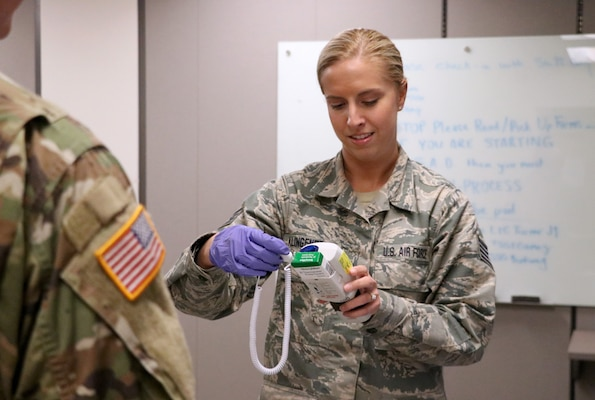 Staff Sgt. Mariah Klingenberg, a force support squadron Airman with the 132d Wing, Iowa Air National Guard, reads a Soldier's temperature before they enter the Joint Emergency Operations Center March 26, 2020. Iowa National Guard Soldiers and Airmen who are on state active duty to support COVID-19 response efforts must have their temperature taken before reporting for work to slow the spread of COVID-19 and protect the health of Iowa National Guard members.