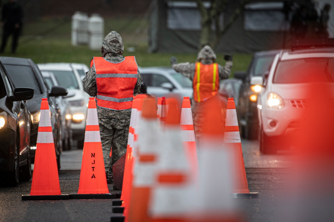 New Jersey Air Guard Airmen from the 108th Wing provide traffic control at a COVID-19 Community-Based Testing Site at the PNC Bank Arts Center in Holmdel, N.J., March 23, 2020.  The testing site, established in partnership with the Federal Emergency Management Agency, is staffed by the New Jersey Department of Health, the New Jersey State Police, and the New Jersey National Guard.