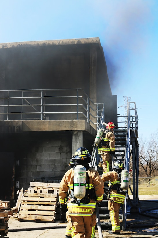 Reserve Citizen Airmen from the 445th Civil Engineer Squadron, Fire and Emergency Services Flight, approach a live fire at the Dayton Fire Department training facilities in Ohio on March 7, 2020. The squadron partnered with the community fire department for the day to meet an annual training requirement for a structure fire. Teams worked in groups of five to maneuver a hose through the building and into the basement where the fire was extinguished. (U.S. Air Force photo/1st Lt. Rachel Ingram)