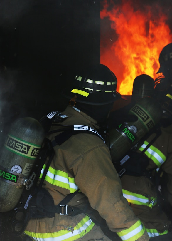 Inside the Dayton Fire Department training facilities, a basement fire blazes while a team of Reserve Citizen Airmen from the 445th Civil Engineer Squadron, Fire and Emergency Services Flight, maneuver a hose through the building. The squadron, based at Wright-Patterson Air Force Base, Ohio, partnered with the community fire department on March 7, 2020 to meet an annual training requirement for a structure fire. (U.S. Air Force photo/1st Lt. Rachel Ingram)
