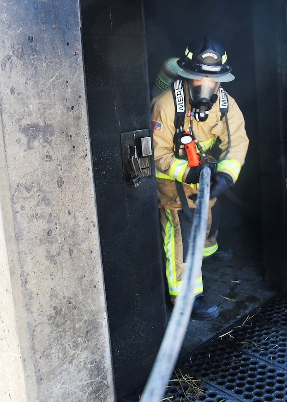 Senior Airman Ryan Guenther, firefighter with the 445th Civil Engineer Squadron, Fire and Emergency Services Flight, feeds a charged hose through an upper-level door at the Dayton Fire Department training facilities on March 7, 2020. Guenther is part of a five-person team honing their communication and maneuvering skills to reach a basement fire in the training building, as part of live structure fire training. (U.S. Air Force photo/1st Lt. Rachel Ingram)