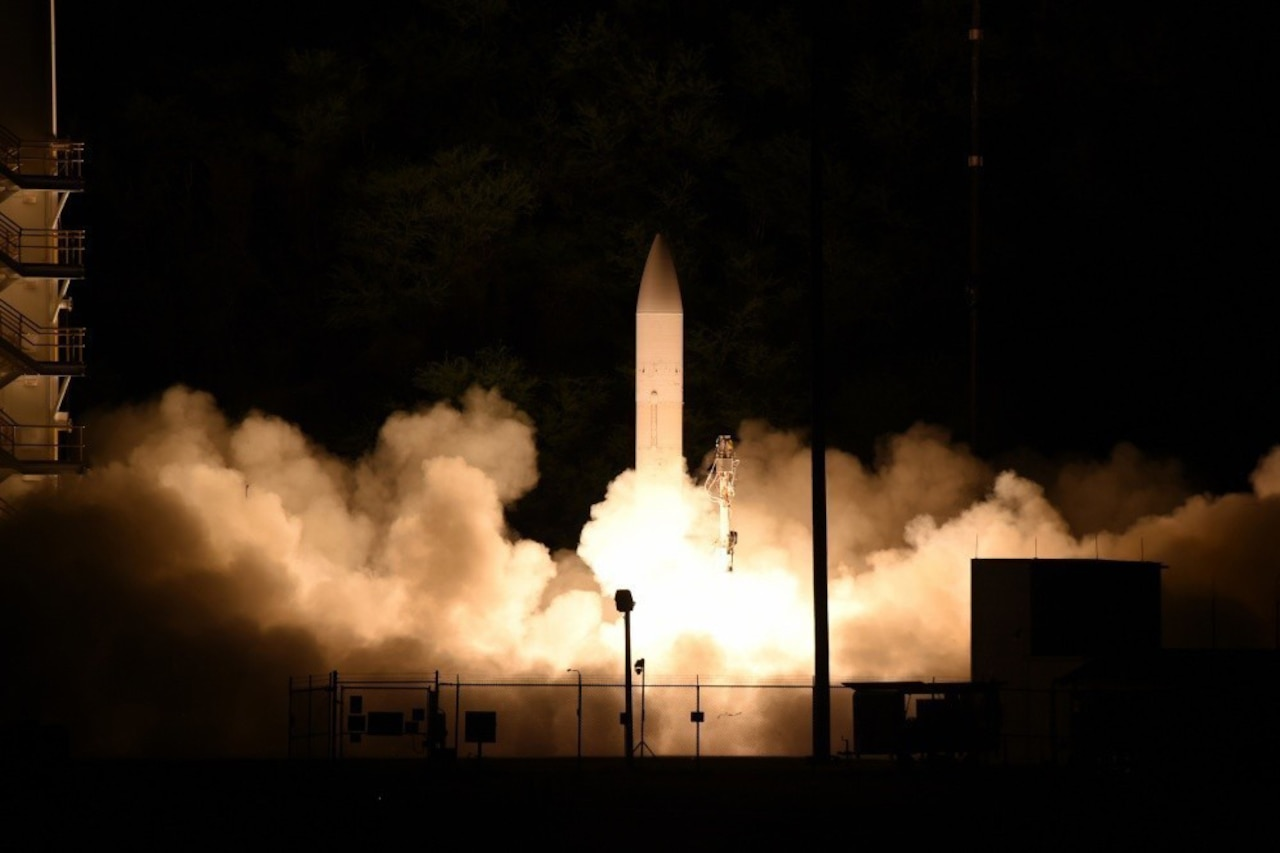 A white rocket launches at night.