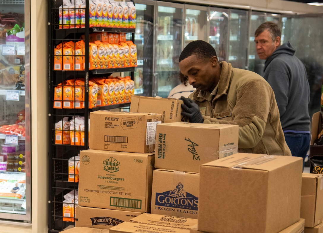 Master Sgt. Mauritius McCall, 436th Security Forces Squadron first sergeant, picks up a box before stocking shelves March 25, 2020, at Dover Air Force Base, Del. The Chiefs Group and first sergeants volunteered at the commissary checking IDs, assisting with social-distancing measures and stocking shelves to help mitigate the spread of COVID-19, reduce confusion and ensure Airmen and their families still had access to essential items. (U.S. Air Force photo by Airman 1st Class Jonathan Harding)