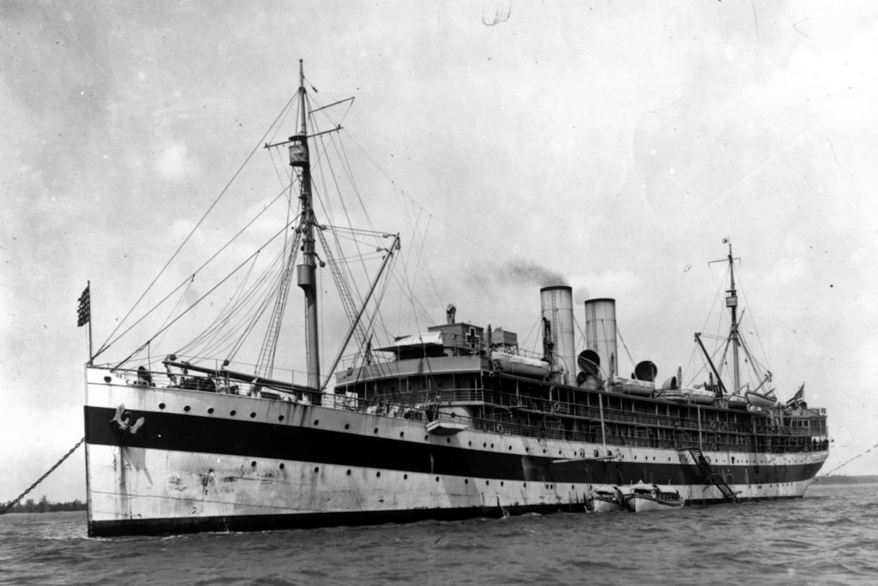Black-and-white image of a large ship at anchor.