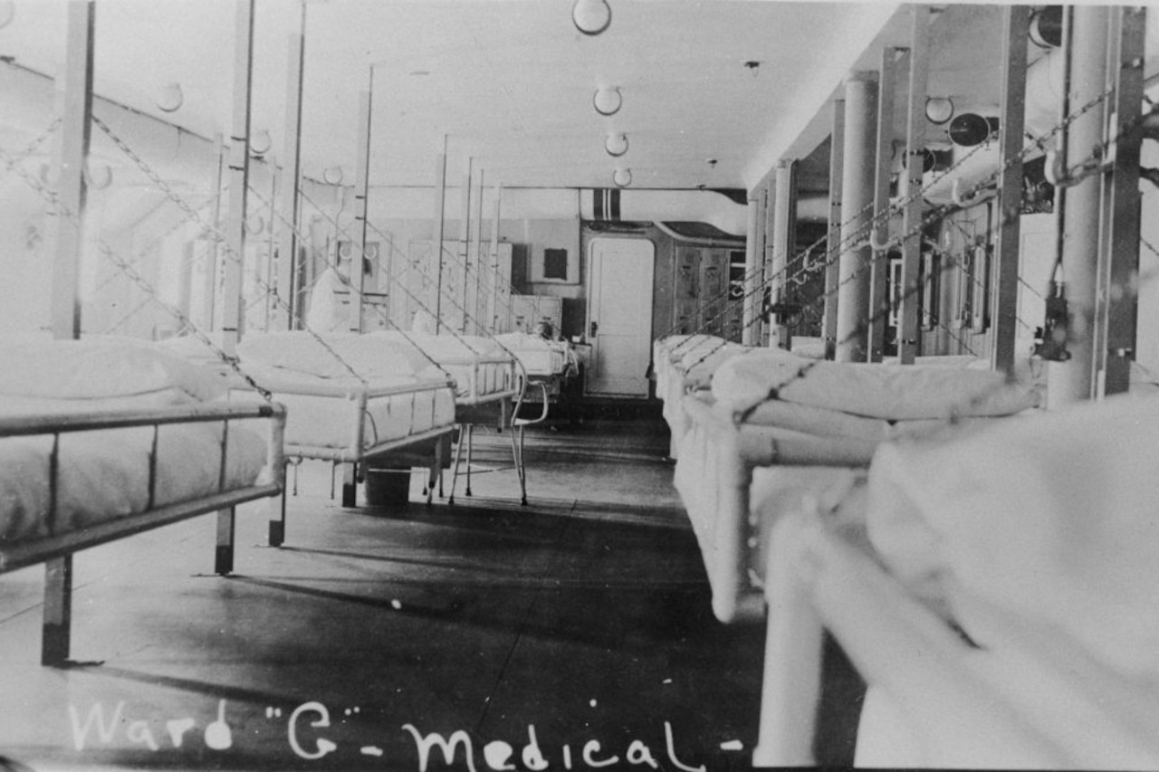 Hospital beds line two walls aboard a ship.