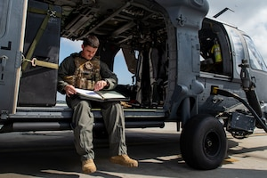 Photo of an Airman reviewing a preflight checklist.